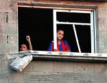 Junger palästinesischer Bub blickt aus einem zerstörten Gebäude
