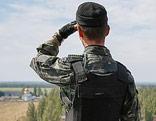 Ein ukrainischer Soldat blickt von einem Dach in die Ferne