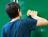 Ein Schüler wischt die Tafel