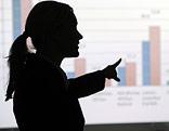 Eine Frau erklärt eine mittels Beamer an die Wand projezierte Statistik