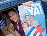 """Frau hält ein Poster mit der Aufschrift """"Freiheit - jetzt"""" aus einem Autofenster"""