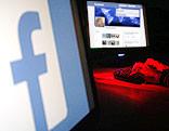 Facebook-user vor einem Computer, davor ein Facebook-Logo