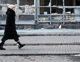 Eine Frau geht in Donezk an einem durch Bomben- und Raketeneinschläge völlig zerstörten Haus vorbei