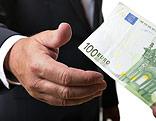 Eine Person im Anzug nimmt einen 100-Euro-Schein
