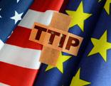 """Flaggen von USA und EU dazwischen ein Pflaster mit der Aufschrift """"TTIP"""""""