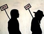 Auf eine Wand gemalte Menschensilhouetten mit Ja- und Nein-Schild