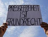 """Demonsrant hält ein Schild mit der Aufschrift """"Pressefreiheit ist Grundrecht"""""""