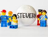 """Legomännchen mit einer Styroporkugel, auf der """"Steuern"""" steht"""