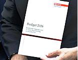 Finanzminister hält Unterlagen zum Budget 2016 in der Hand