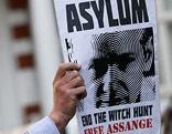 Unterstützer von Wikileaks hält Plakat hoch