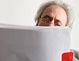 Älterer Mann liest in Unterlagen