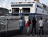 Migranten stehen vor einer Fähre