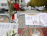 An einer Absperrung sind Blumen und Gedenkzettel angebracht