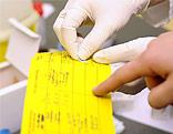 Eine Amtsärztin klebt den Nachweis einer Impfung in einen Impfpass ein