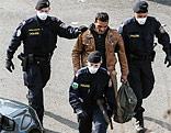 Polizisten mit Atemschutzmasken führen einen Mann ab