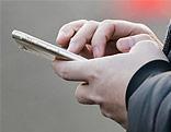 Mann hält Mobiltelefon
