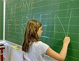 """Eine Schülerin schreibt """"Schöne Ferien"""" auf die Tafel"""