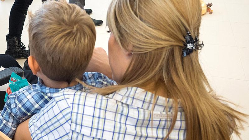 Mutter mit Kindergartenkind auf dem Arm