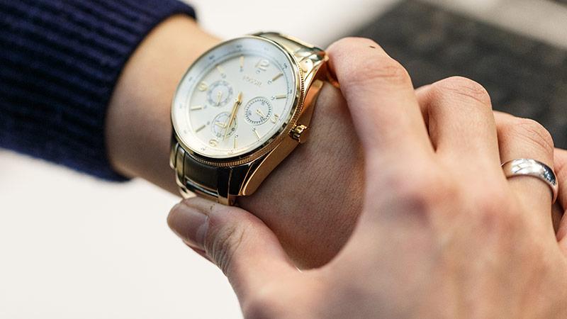 Junge Frau blickt auf die Uhr