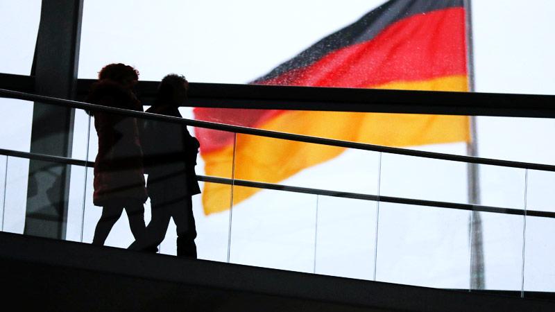Silhoutten zweier Frauen gehen eine Treppe hinab, dahinter die Deutschlandfanhe