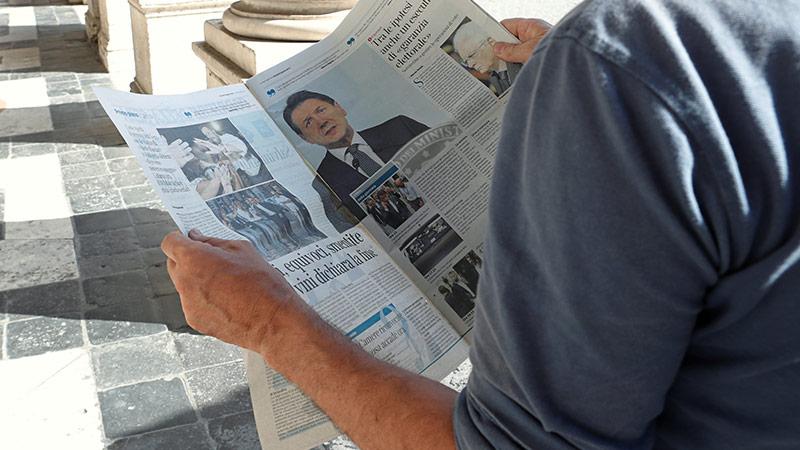 Mann liest Zeitung in Italien