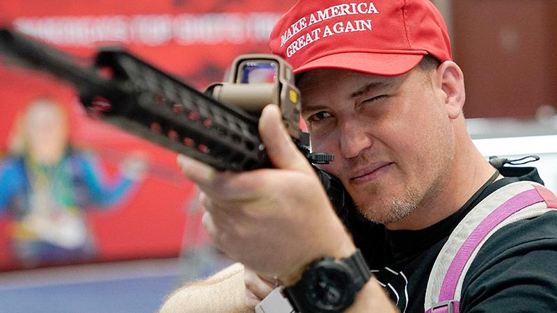 """Ein Mann hat eine Kappe mit der Aufschrift """"Make America great again"""" auf, während er eine Waffe während einer NRA-Veranstaltung in der Hand hält"""