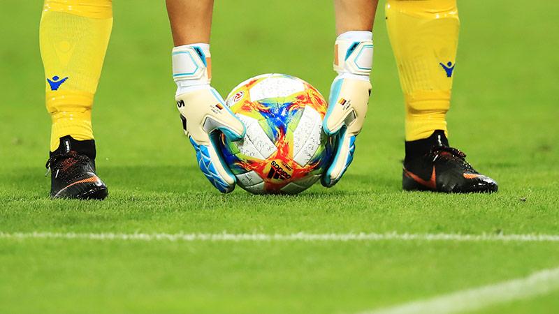 Tormann hebt einen Fußball auf
