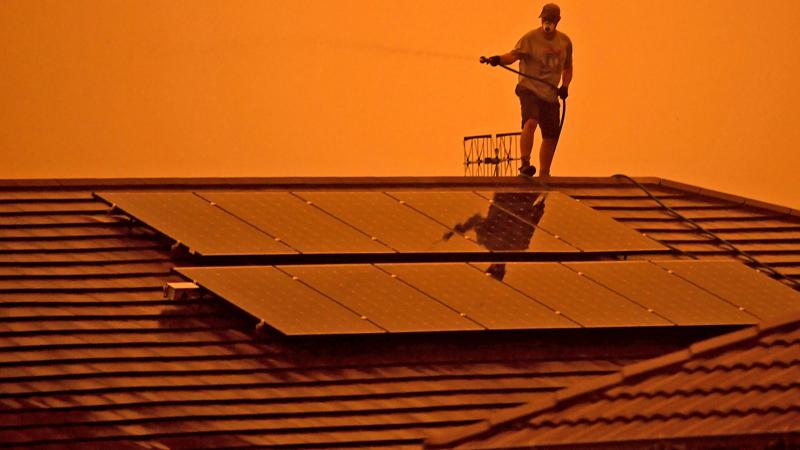 Feuerwehrmann bei Löscharbeiten auf einem Hausdach