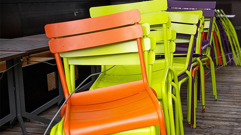 Übereinander gesatpelte und zusammengekettete Sessel eines geschlossenen Lokals