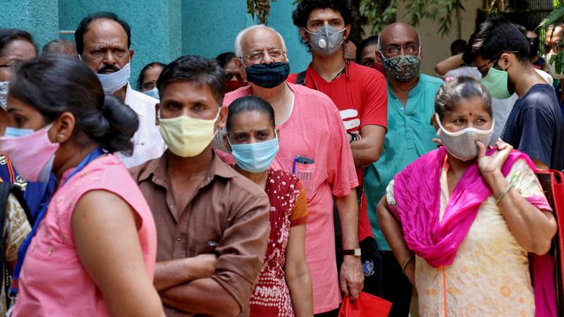 Indische Frauen und Männer stellen sich für eine Corona-Impfung an