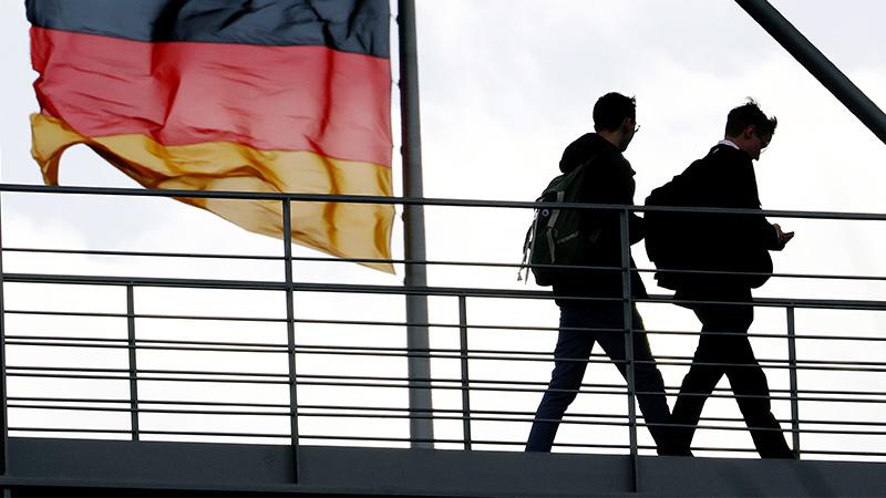 Menschen gehen an einer deutschen Fahne vorbei