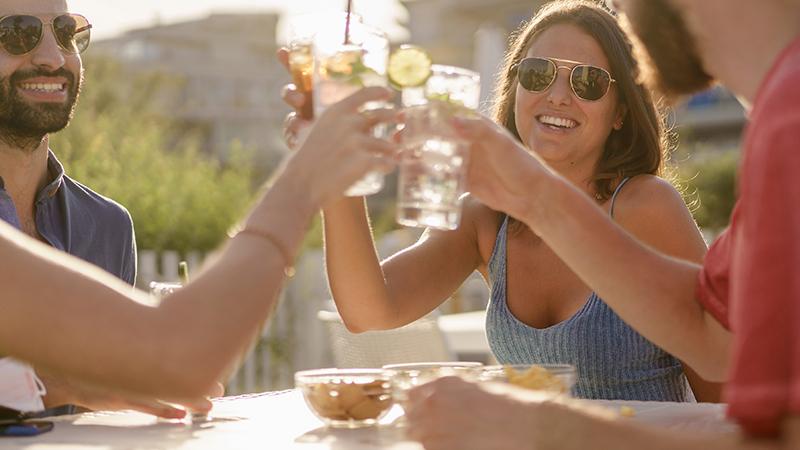 Menschen stoßen mit Cocktails an